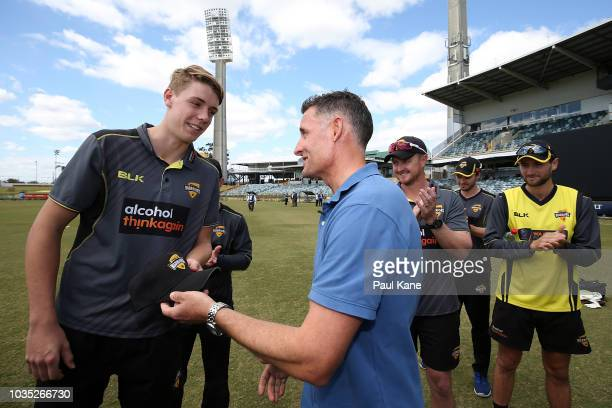 Mike Hussey presents a cap to Cameron Green of WA during the JLT One Day Cup match between Western Australia and New South Wales at the WACA on...