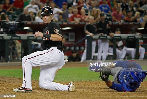Mike Jacobs of the Arizona Diamondbacks looks to the home plate umpire for a call after sliding home ahead of the tag of catcher Wellington Castillo...