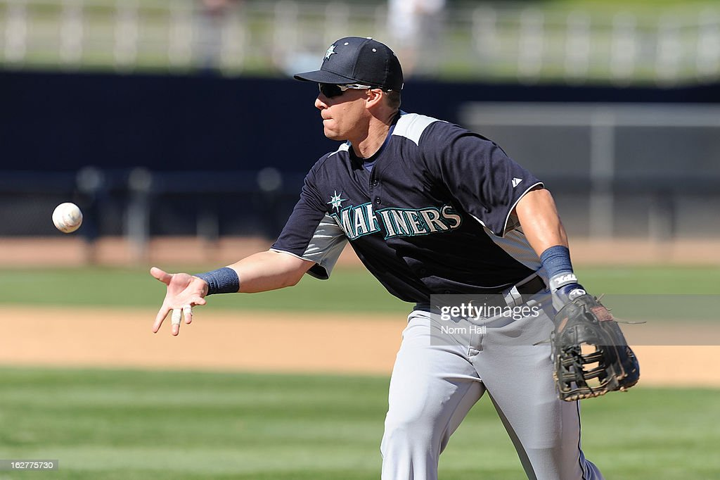 Mike Jacobs #35 of the Seattle Mariners underhands the ball to first base against the Milwaukee Brewers at Maryvale Baseball Park on February 26, 2013 in Maryvale, Arizona.