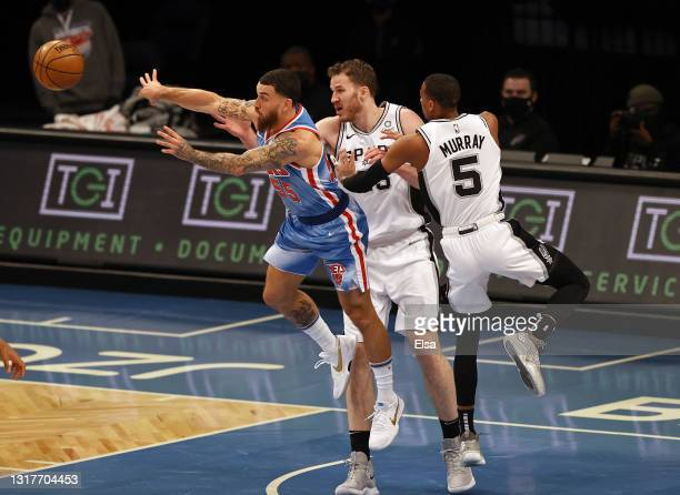 Mike James of the Brooklyn Nets passes the ball as Jakob Poeltl and Dejounte Murray of the San Antonio Spurs defend in the first quarter at Barclays...