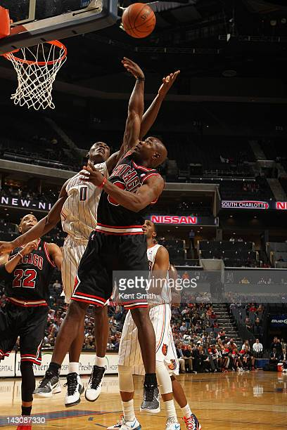 Mike James of the Chicago Bulls shoots against Bismack Biyombo of the Charlotte Bobcats at the Time Warner Cable Arena on April 18 2012 in Charlotte...