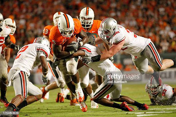 Mike James of the Miami Hurricanes is stopped short of the goal line by Zach Boren and Christian Bryant of the Ohio State Buckeyes on September 17...