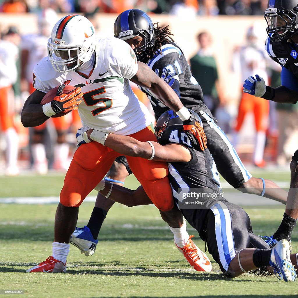 Mike James #5 of the Miami Hurricanes runs against Dwayne Norman #40 of the Duke Blue Devils at Wallace Wade Stadium on November 24, 2012 in Durham, North Carolina.