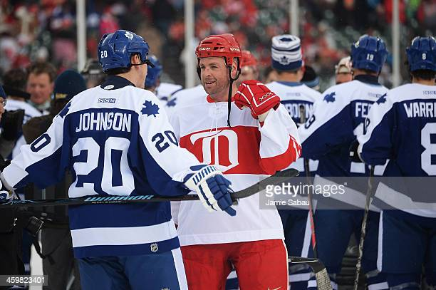 Mike Johnson of the Toronto Maple Leafs talks with Aaron Ward of the Detroit Red Wings following the end of the first game of the 2013 Hockeytown...