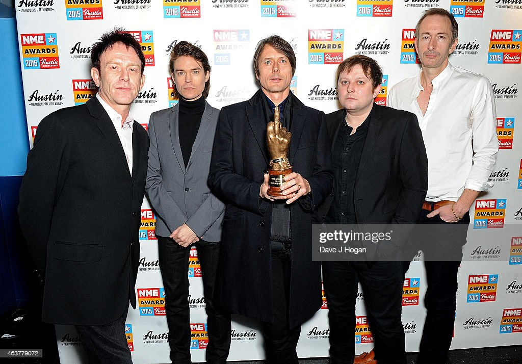 Mike Joyce, Richard Oakes, Brett Anderson, Simon Gilbert and Mat Osman of Suede receive the God Like Genius Award in the winners room at the NME Awards at Brixton Academy on February 18, 2015 in London, England.