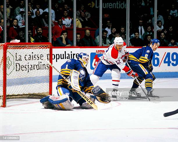 Mike Keane of the Montreal Canadiens skates between goaltender Jacques Cloutier and defenseman Phil Housley of the Buffalo Sabres in a game at the...
