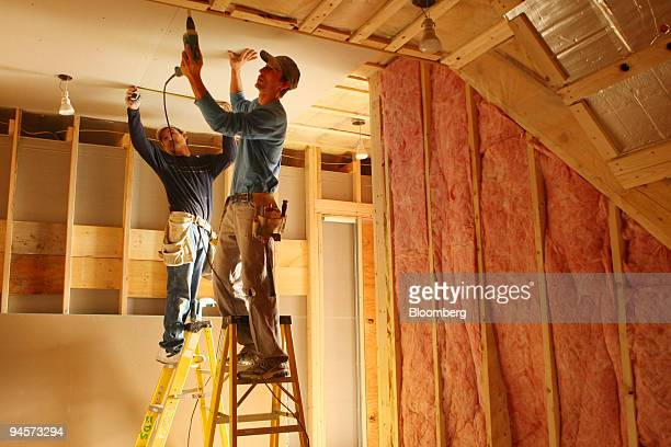 Mike Kelly left and Seth Warner hang drywall in a new home under construction in Peacham Vermont US on Tuesday Oct 30 2007 Spending on US...