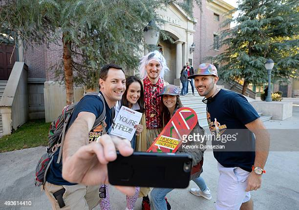 Mike Knell dressed as the character Dr Emmett Brown Stephanie Knell and Jackie Peters pose with fellow fans on steps of Hill Valley Courthouse Square...