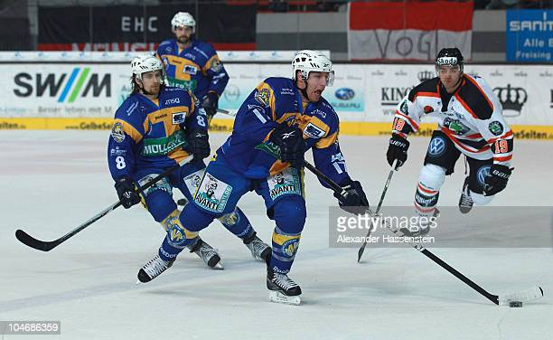Mike Kompon of Muenchen vies for the puck with Ken Magowan of Wolfsburg during the DEL match between EHC Muenchen and Grizzly Adams Wolfsburg at...