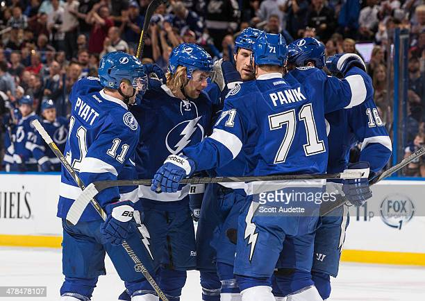Mike Kostka of the Tampa Bay Lightning celebrates his goal with teammates Tom Pyatt and Richard Panik during the first period against the Florida...