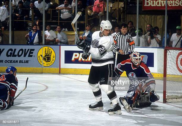 Mike Krushelnyski of the Los Angeles Kings screens goalie Bill Ranford of the Edmonton Oilers as Kevin Lowe of the Oilers and referee Mick McGeough...