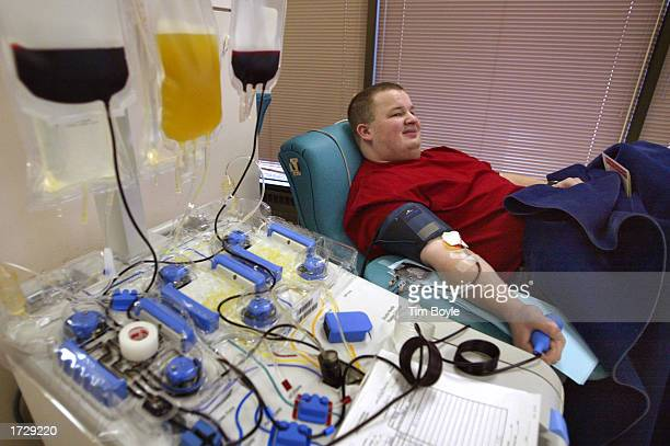 Mike Kulis lies partially under a blanket as he donates blood platelets at LifeSource Blood Services January 16 2003 in Glenview Illinois Significant...
