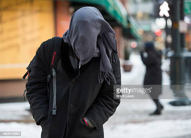 Mike Longmire from Los Angeles walks across Tremont Place while covering his face with a scarf Tuesday December 30 2014 at the intersection of 17th...