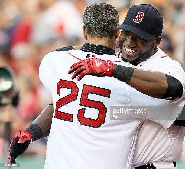 Mike Lowell former Red Sox third baseman is greeted by former teammate David Ortiz of the Boston Red Sox before the game against the Seattle Mariners...