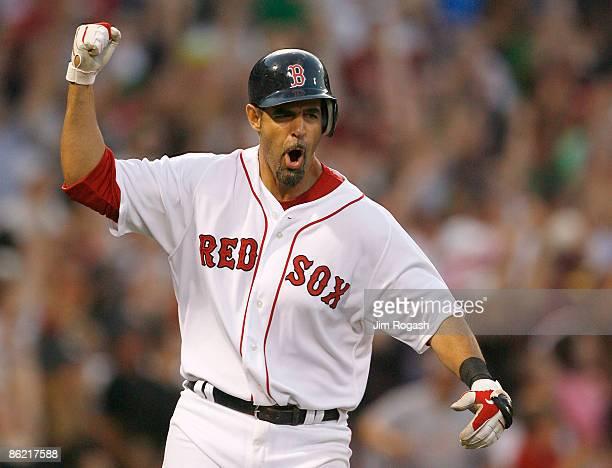 Mike Lowell of the Boston Red Sox celebrates as he rounds the bases after hitting a home run against the New York Yankees at Fenway Park April 25 in...