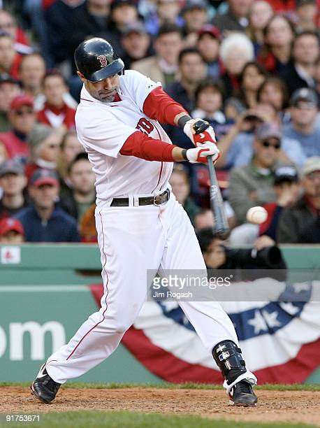 Mike Lowell of the Boston Red Sox hits a RBI single in the eighth inning against the Los Angeles Angels of Anaheim in Game Three of the ALDS during...