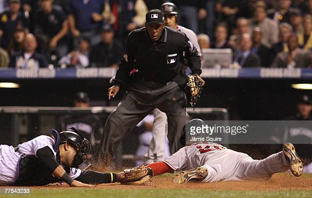 Mike Lowell of the Boston Red Sox slides in safely to home past the tag of Yorvit Torrealba of the Colorado Rockies to score in the fifth inning of...