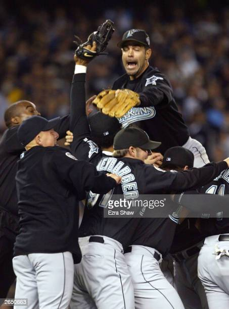 Mike Lowell of the Florida Marlins jumps on top of the pile of his teammates after defeating the New York Yankees 20 to win game six of the Major...