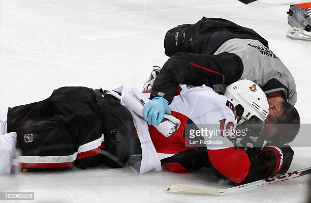 Mike Lundin of the Ottawa Senators is tended to by a trainer after an openice hit by Harry Zolnierczyk of the Philadelphia Flyers on March 2 2013 at...