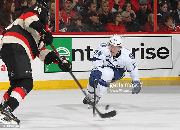 Mike Lundin of the Ottawa Senators makes a pass as Ondrej Palat of the Tampa Bay Lightning tries to deflect the puck on March 23 2013 at Scotiabank...