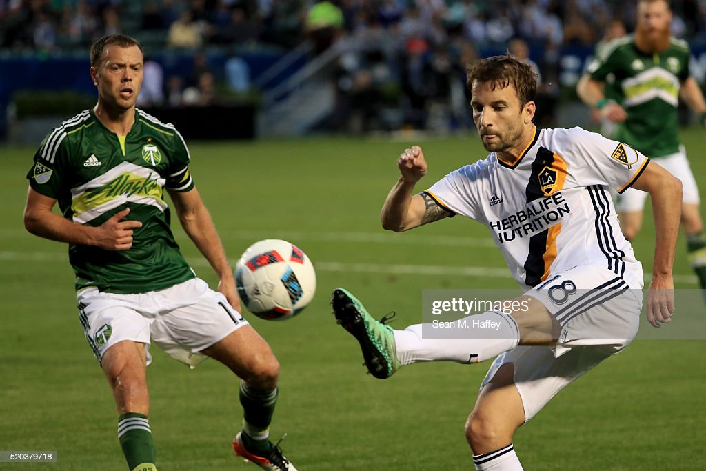 Mike Magee #18 of Los Angeles Galaxy shoots on goal against the Los Angeles Angels of Anaheim Jack Jewsbury #13 of the Portland Timbers defend during the first half of their MLS match at StubHub Center on April 10, 2016 in Carson, California.