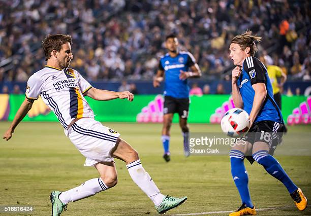 Mike Magee of Los Angeles Galaxy shoots on goal as Kip Colvey of San Jose Earthquakes defends during Los Angeles Galaxy's MLS match against San Jose...