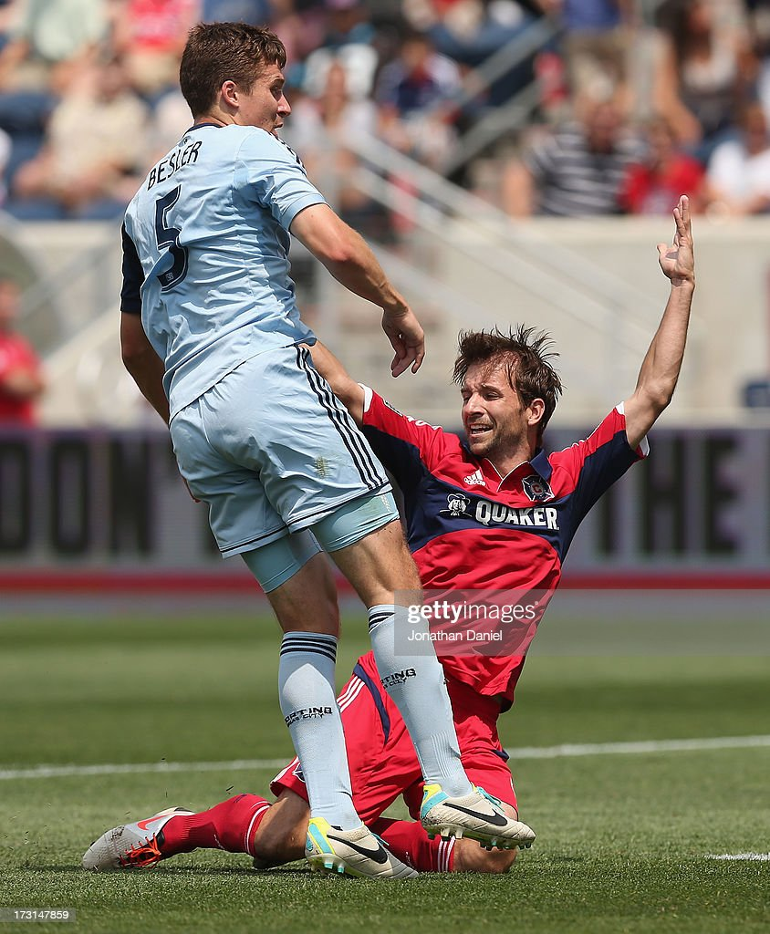 Mike Magee #9 of the Chicago Fire is hit by Matt Besler #5 of Sporting Kansas City during an MLS match at Toyota Park on July 7, 2013 in Bridgeview, Illinois. Sporting Kansas City defeated the Fire 2-1.