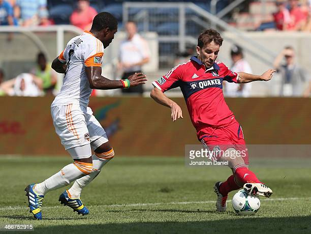 Mike Magee of the Chicago Fire works against Kofi Sarkodie of the Houston Dynamo during an MLS match at Toyota Park on September 1 2013 in Bridgeview...