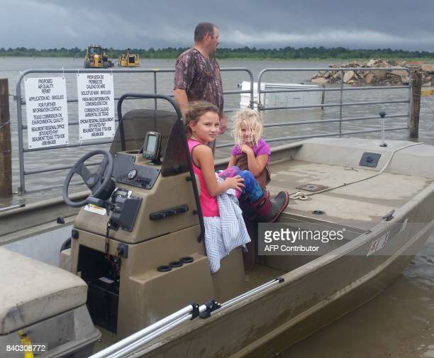 Mike Magee stands next to his boat with his daughters inside before setting out on a mission to rescue a friend and her four children from heavy...