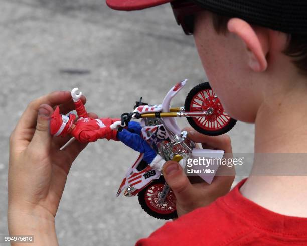 Mike Manley of California plays with a Nitro Circus motorcycle toy while waiting for Travis Pastrana to peform during HISTORY's Live Event 'Evel...