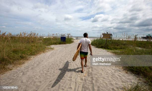 Mike Martin heads out to Folly Beach to catch a few waves on September 13 2018 in Charleston South Carolina United States Coastal cities in North...