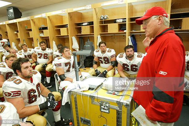 Mike Martz of the San Francisco 49ers addresses the offensive line in the locker room at halftime during the NFL game against the Chicago Bears at...