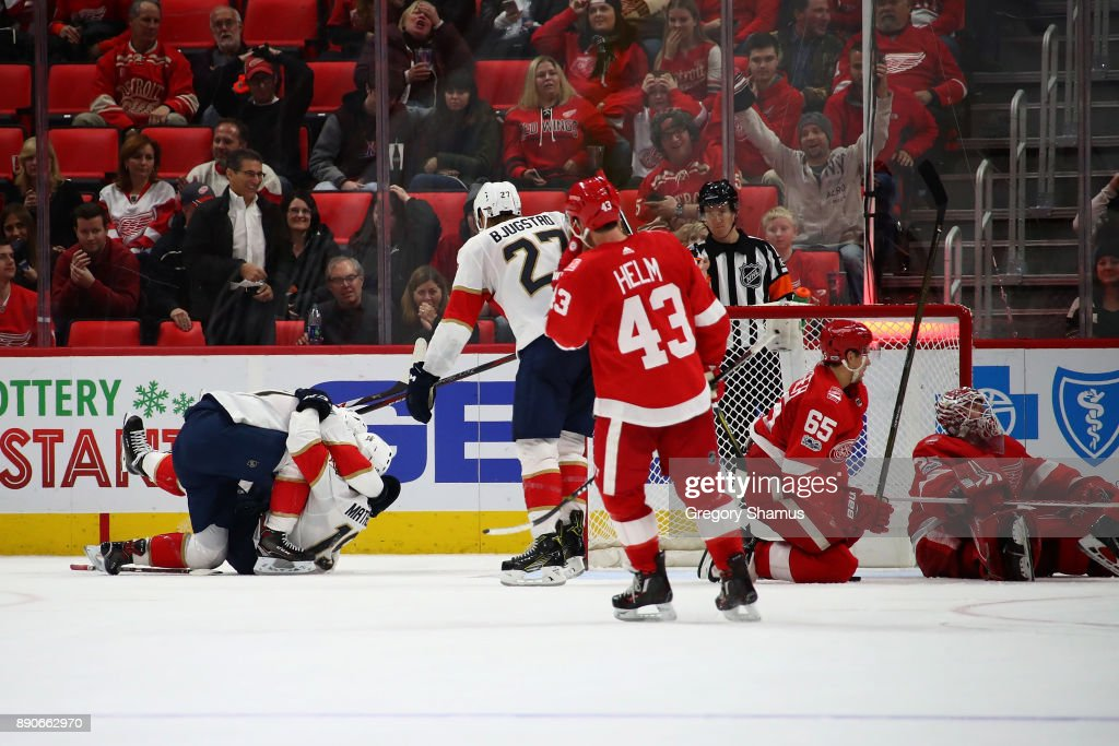 Mike Matheson #19 of the Florida Panthers celebrate his game winning overtime goal with Jonathan Huberdeau #11 while playing the Detroit Red Wings at Little Caesars Arena on December 11, 2017 in Detroit, Michigan.