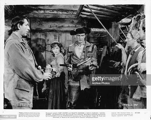 Mike Mazurki has gun pulled on him and his men by Gary Cooper as Paulette Goddard watches in a scene from the film 'Unconquered' 1947
