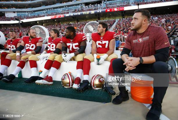 Mike McGlinchey Weston Richburg Laken Tomlinson Justin Skule and Joe Staley of the San Francisco 49ers sit on the sideline during the game against...