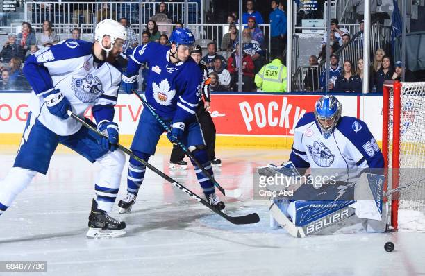 Mike McKenna of the Syracuse Crunch stops a shot as Kirby Rychel of the Toronto Marlies and Mathieu Brodeur of the Crunch look on during game 6...