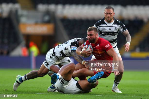 Mike McMeeken of Catalans Dragons is tackled by Hull FC's Manu Ma'u and Chris Satae during the Betfred Super League round 6 match between Hull FC and...