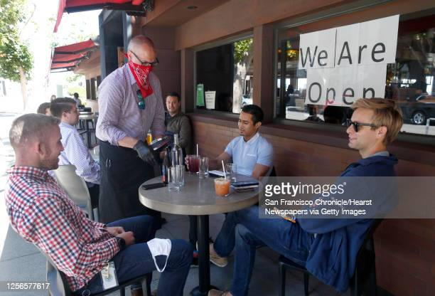 Mike Mendez-Gatewood serves beverages to a group having lunch outdoors at Fog City Diner in San Francisco, Calif. On Tuesday, July 7, 2020. Fog City...