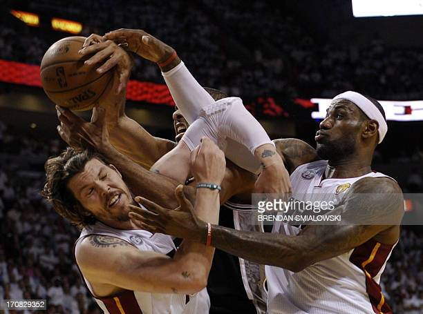 Mike Miller and LeBron James of the Miami Heat vie for a rebound with Tim Duncan of the San Antonio Spurs during the first half in Game 6 of the NBA...