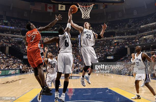 Mike Miller of the Memphis Grizzlies pulls down a rebound with Eddie Jones of the Memphis Grizzlies and Gerald Wallace of the Charlotte Bobcats on...