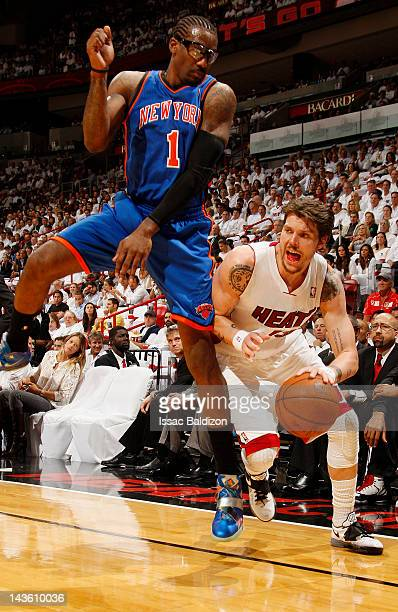 Mike Miller of the Miami Heat dribbles the ball around a leaping Amare Stoudemire of the New York Knicks in Game Two of the Eastern Conference...