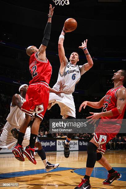 Mike Miller of the Washington Wizards shoots against Taj Gibson and Brad Miller of the Chicago Bulls at the Verizon Center on February 22 2010 in...