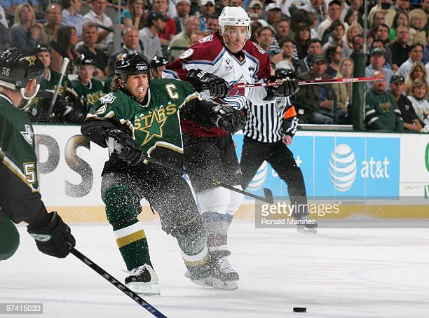 Mike Modano of the Dallas Stars and Joe Sakic of the Colorado Avalanche battle for the puck during the second period of Game two of the NHL Western...