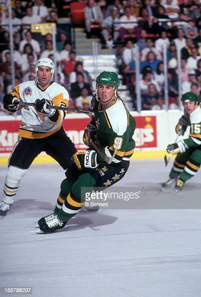 Mike Modano of the Minnesota North Stars skates on the ice as he is hooked by Gordie Roberts of the Pittsburgh Penguins during the 1991 Stanley Cup...