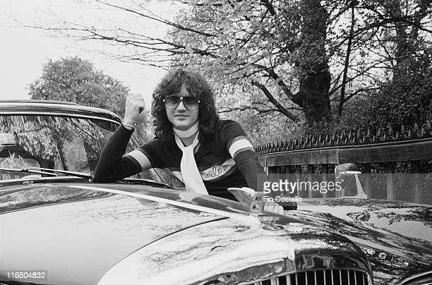 Mike Moran British musician songwriter and record producer wearing a white scarf while leaniing on the bonnet of his Bentley car in London England...