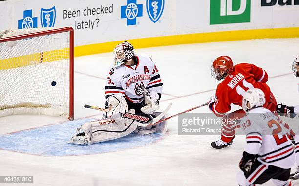 Mike Moran of the Boston University Terriers scores against Clay Witt of the Northeastern Huskies during the first period of NCAA hockey in the...