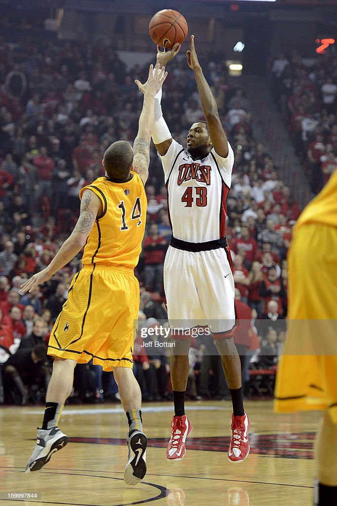 Mike Moser #43 of the UNLV Rebels puts up a shot against Josh Adams #14 of the Wyoming Cowboys at the Thomas & Mack Center January 24, 2013 in Las Vegas, Nevada.