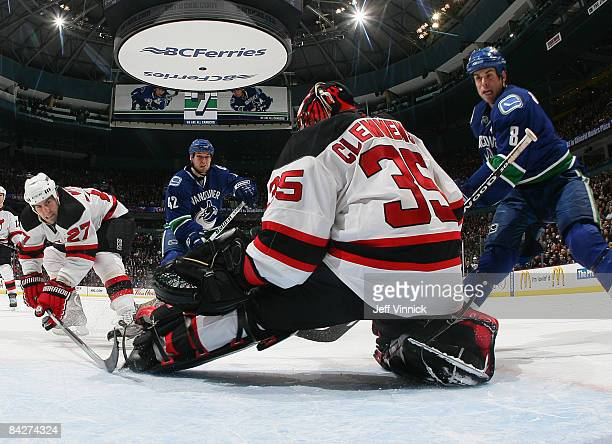 Mike Mottau of the New Jersey Devils and Kyle Wellwood and Willie Mitchell of the Vancouver Canucks look on as Scott Clemmensen of the New Jersey...