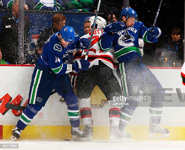 Mike Mottau of the New Jersey Devils gets sandwiched between Alex Burrows of the Vancouver Canucks and Ryan Kesler during their game at General...