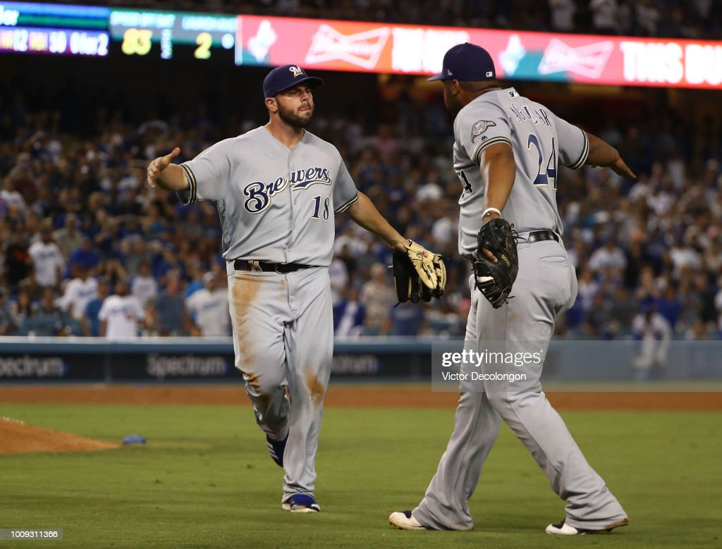 Mike Moustakas #18 and Jesus Aguilar #24 of the Milwaukee Brewers celebrate after Moustakas fielded a throw from third base to Aguilar at first base with the bases loaded to end the eighth inning of the MLB game against the Los Angeles Dodgers at Dodger Stadium on August 1, 2018 in Los Angeles, California. The Dodgers defeated the Brewers 6-4.